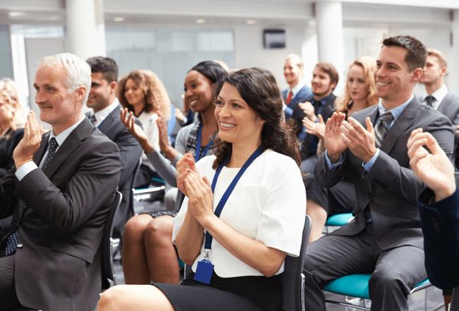 Group of people applauding at a healthcare compliance auditing conference